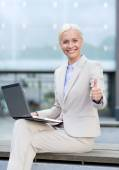 Smiling businesswoman working with laptop outdoors — Stock Photo