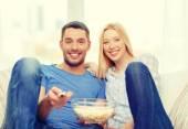 Sonriente pareja con palomitas viendo cine en casa — Foto de Stock