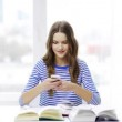 Smiling student girl with smartphone and books — Stock Video #61049255