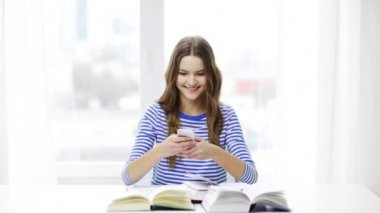 Smiling student girl with smartphone and books — Stock Video