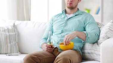 Man with popcorn and beer changing tv channels — Video Stock