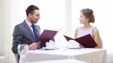 Smiling couple with menus at restaurant — Stock Video