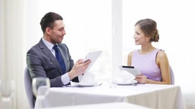 Couple with menus on tablet pc at restaurant — Stock Video