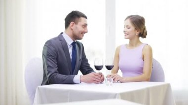 Young couple with glasses of wine at restaurant — Stock Video