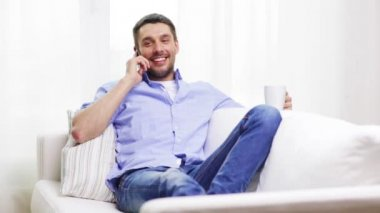 Laughing man with smartphone at home — Stock Video