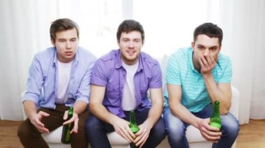 Upset male friends with beer watching tv at home — Stock Video