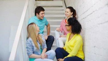 Uśmiechający się uczniowie siedzący na schodach i mówienie — Wideo stockowe