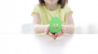 Zbliżenie: uśmiechający się dziewczynka gospodarstwa dom papieru — Wideo stockowe
