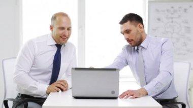 Dos empresarios sonrientes con el portátil en la oficina — Vídeo de stock