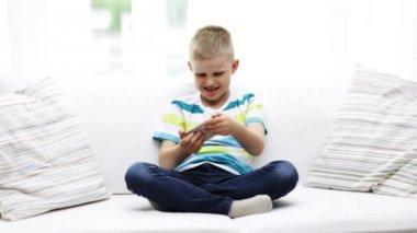 Uśmiechnięty chłopiec bawi się w domu smartphone — Wideo stockowe