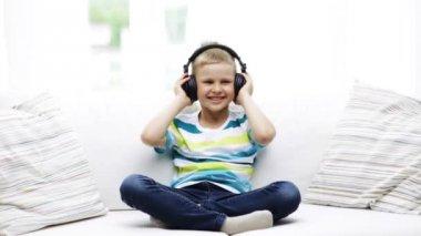 Uśmiechnięty chłopczyk w słuchawki w domu — Wideo stockowe