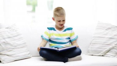Smiling little schoolboy reading book at home — Stock Video