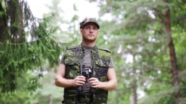 Young soldier or hunter with binocular in forest — Stock Video