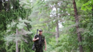 Young soldier or hunter with gun in forest — Vídeo stock