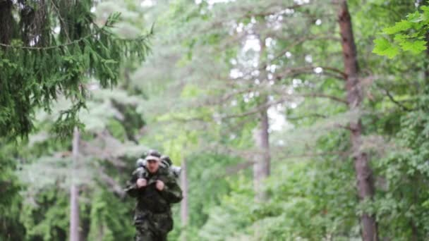 Young soldier with backpack in forest — Vidéo