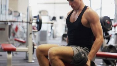 Young man with dumbbell in gym — Stockvideo
