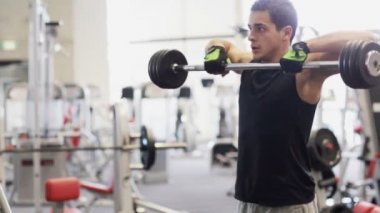 Young man with dumbbell in gym — 图库视频影像