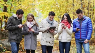 Smiling friends with smartphones and tablet pc — 图库视频影像