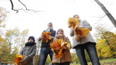 Happy family playing with autumn leaves in park — Vídeo de stock
