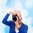 Smiling woman taking picture with digital camera — Stock Photo #61595215