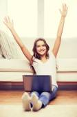 Smiling teenage girl with laptop computer at home — Stock Photo