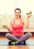 Smiling teenager with green salad and hamburger — Stock Photo