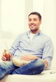 Smiling man with beer and popcorn at home — Stock Photo