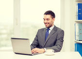 Smiling businessman with laptop and coffee — Stock Photo