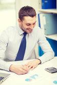Lachende zakenman met laptop en documenten — Stockfoto