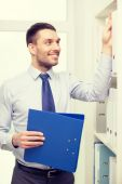 Handsome businessman picking folder at office — Stock Photo
