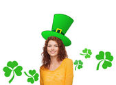 Smiling teen girl in green top hat with shamrock — Stock Photo