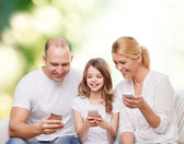 Happy family with smartphones — Stock Photo