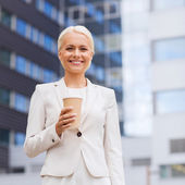 Smiling businesswoman with paper cup outdoors — Stock Photo