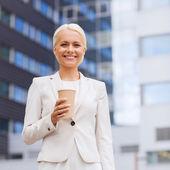Glimlachende zakenvrouw met papier kop buitenshuis — Stockfoto