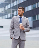 Young serious businessman with paper cup outdoors — Stock Photo