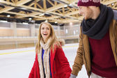 Happy couple holding hands on skating rink — Stock Photo