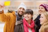 Happy friends taking selfie on skating rink — Stock Photo