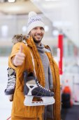 Happy young man showing thumbs up on skating rink — Stock Photo
