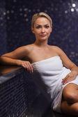 Beautiful young woman sitting in bath towel — Zdjęcie stockowe