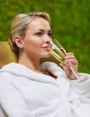 Beautiful young woman drinking champagne at spa — Stock Photo