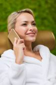 Beautiful young woman with smartphone at spa — Stock Photo