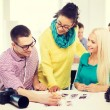 Smiling team with printed photos working in office — Stock Photo #61655397