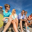 Group of smiling friends sitting on city street — Stock Photo #61658455