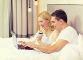 Couple in bed with laptop computer and credit card — Stock Photo