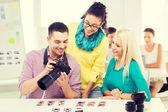 Lachende team met fotocamera werken in office — Stockfoto