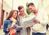 Group of smiling friends with city guide and map — Stock fotografie