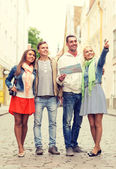 Group of smiling friends with map and photocamera — Stockfoto