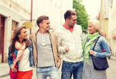 Group of smiling friends walking in the city — Foto de Stock
