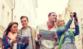 Groep vrienden met city guide, kaart en camera — Stockfoto
