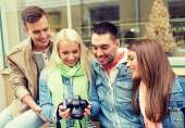 Group of smiling friends with digital photocamera — Stockfoto